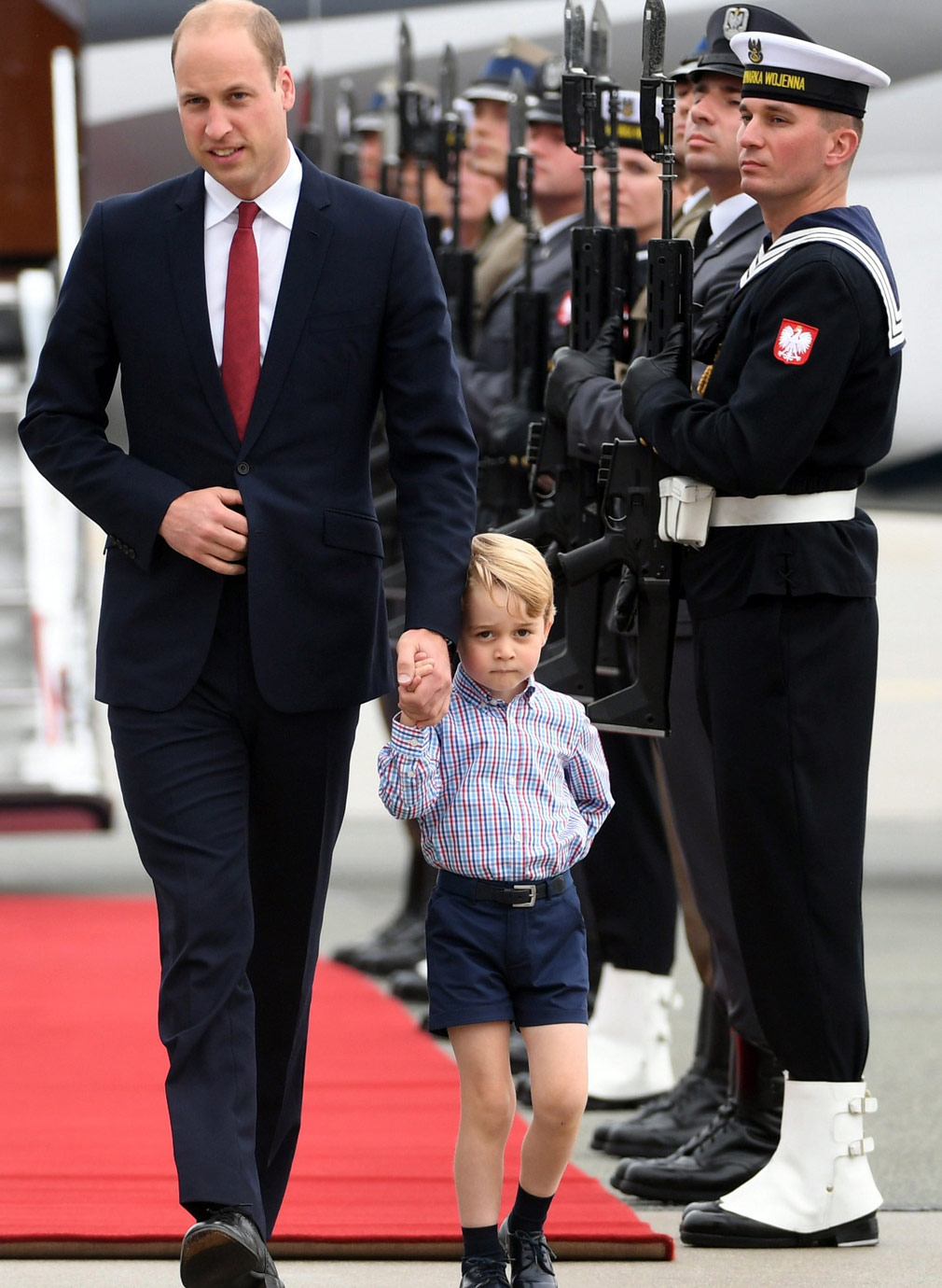 Prince George shies away from the cameras with his father Prince William. (AAP)