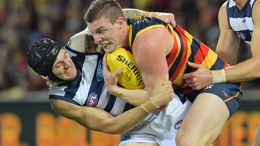 Adelaide's Josh Jenkins is nabbed by Geelong's Tom Stewart on Friday night. (AAP)