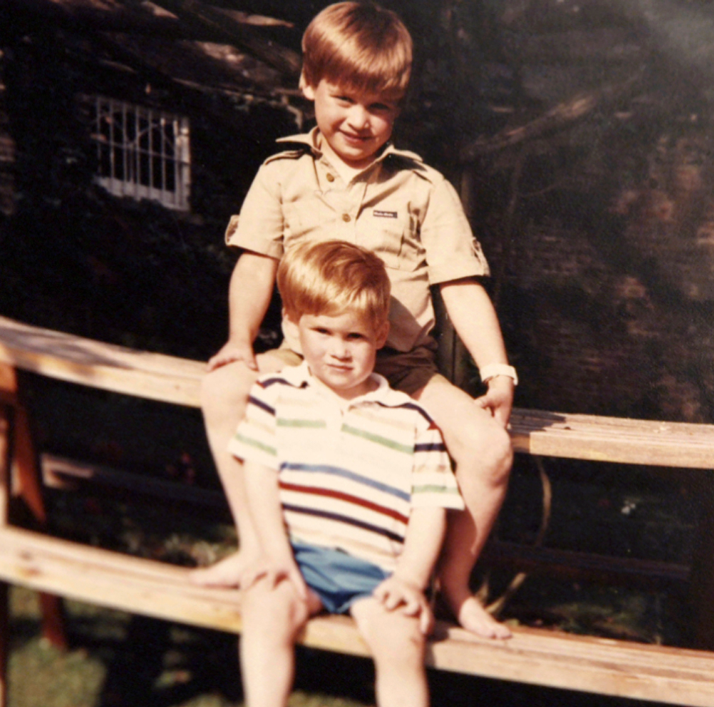 Prince William and Prince Harry sit on a picnic bench together. (Kensington Palace)