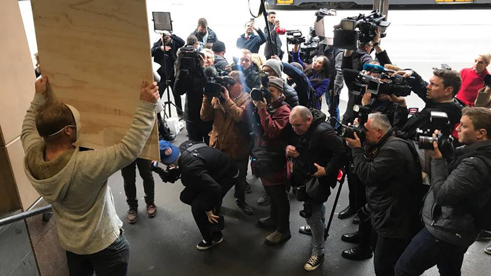 Reporters surround a demonstrator outside court. (Image: Sean Davidson)