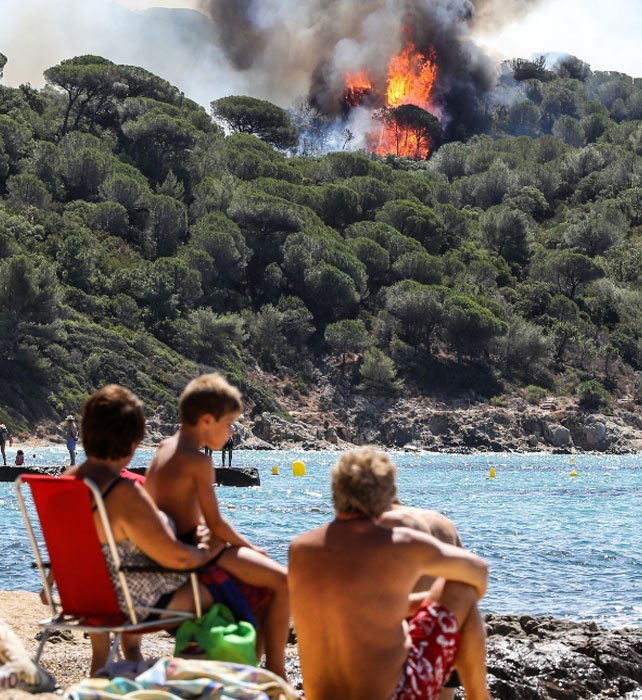 People enjoy the beach as they look at a forest fire in La Croix-Valmer, near Saint-Tropez. (AFP)