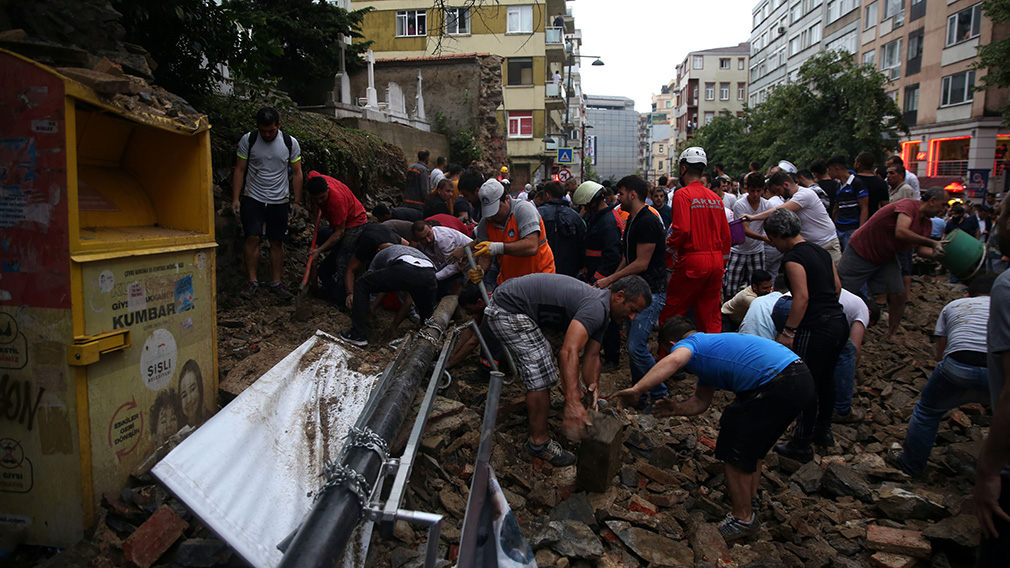 Volunteers try to rescue two injured people who are trapped in the wreckage of a retaining wall. (AFP)