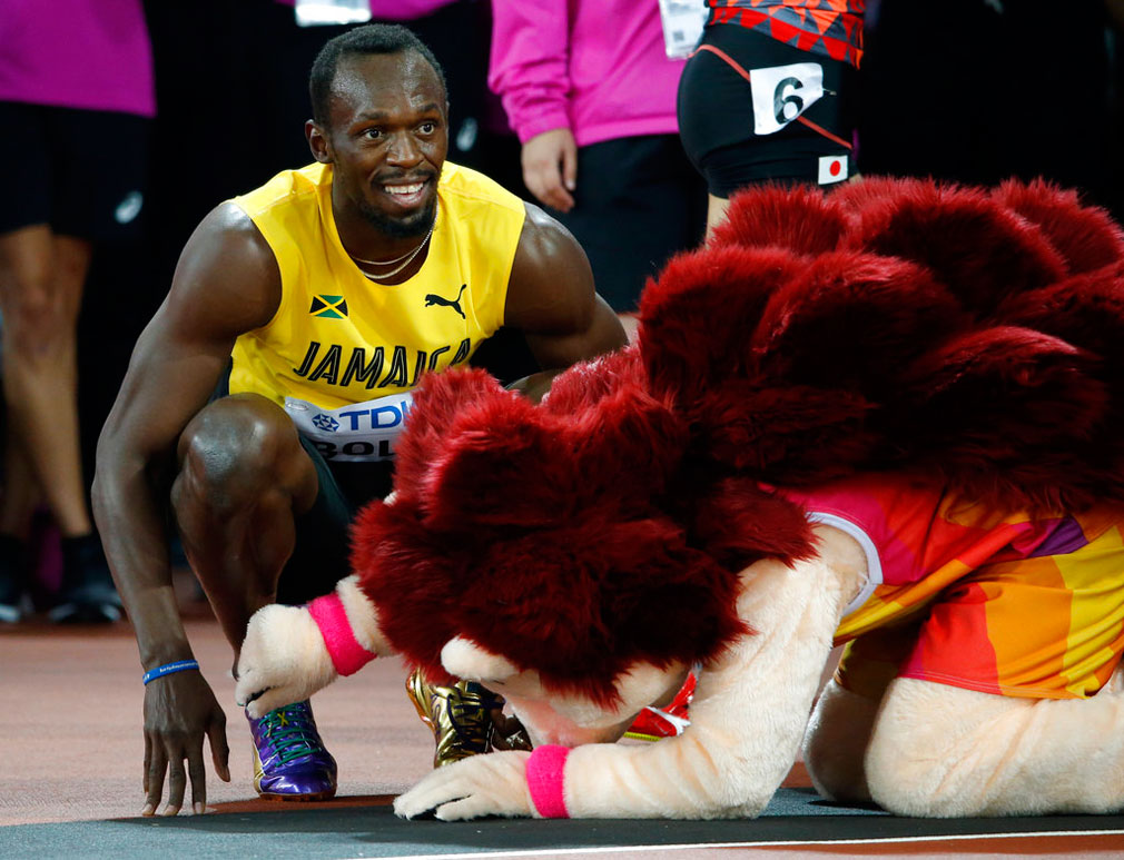 Bolt smiles next to mascot Hero the Hedgehog after his men's 100m heat the World Athletics Championships. (Image: AP Photo/Matthias Schrader)