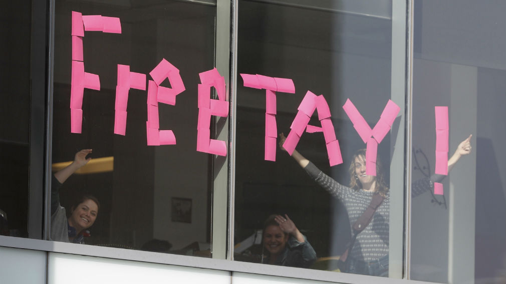 Workers put up sign in support of pop singer Taylor Swift in an office building across the street from the federal courthouse in Denver. (AAP)