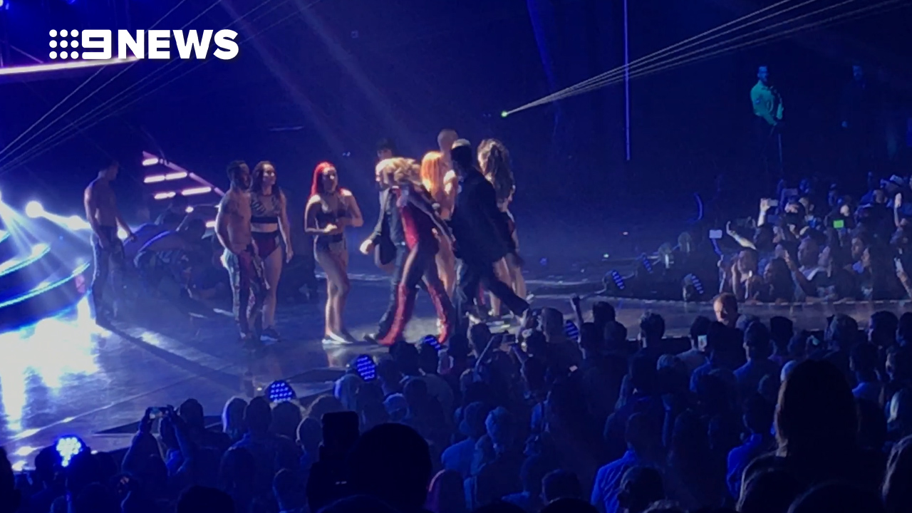 Spears is ushered off stage by security