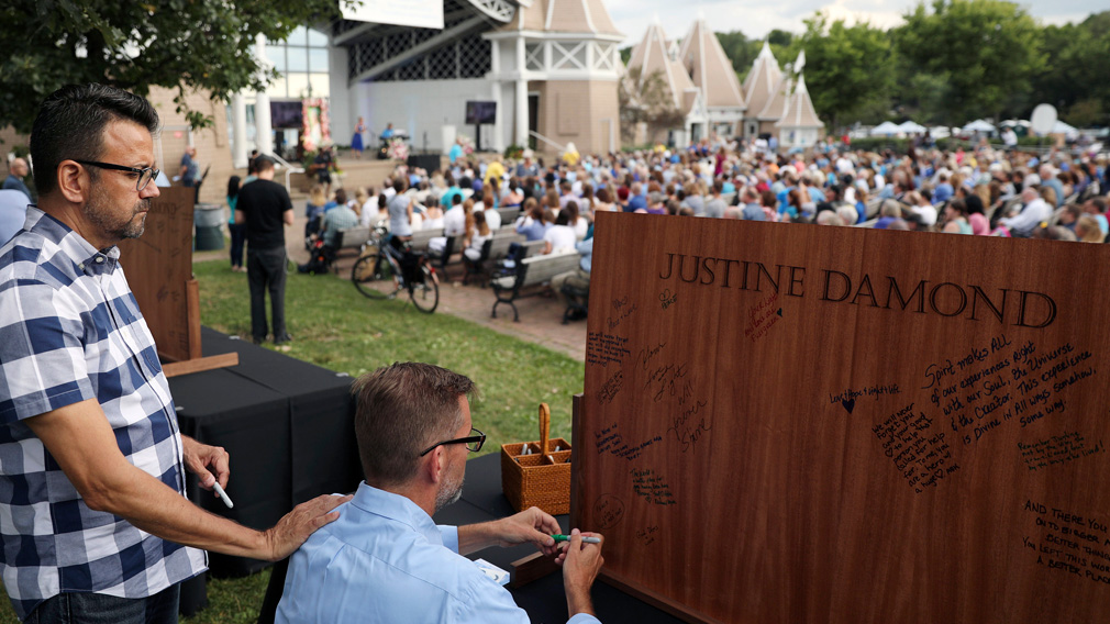 Sen. Scott Dibble, DFL - Minneapolis, signs a wooden board as his husband Richard Leyva put his hand on his shoulder during the memorial service for Justine Damond. (AAP)