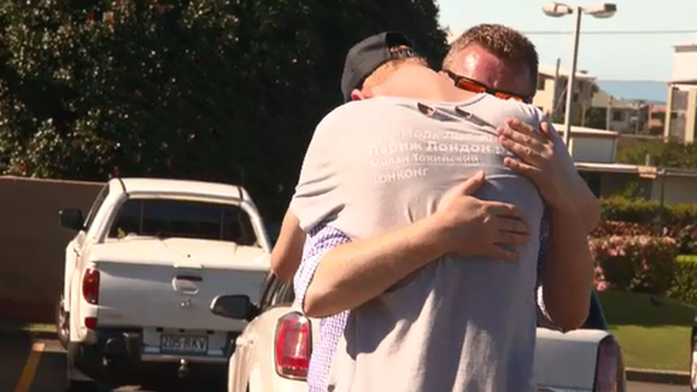 Joshua embraces his dad Andy after returning to the Redcliffe McDonald's where he was felled. (9NEWS)