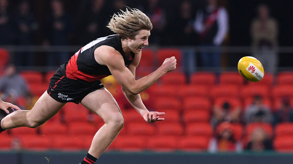 Dyson Heppell gets a hand pass away for Essendon against Gold Coast. (AAP)