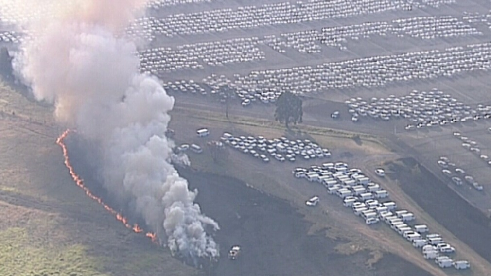 The fire threatened the car yard and the Odyssey House building. (9NEWS)