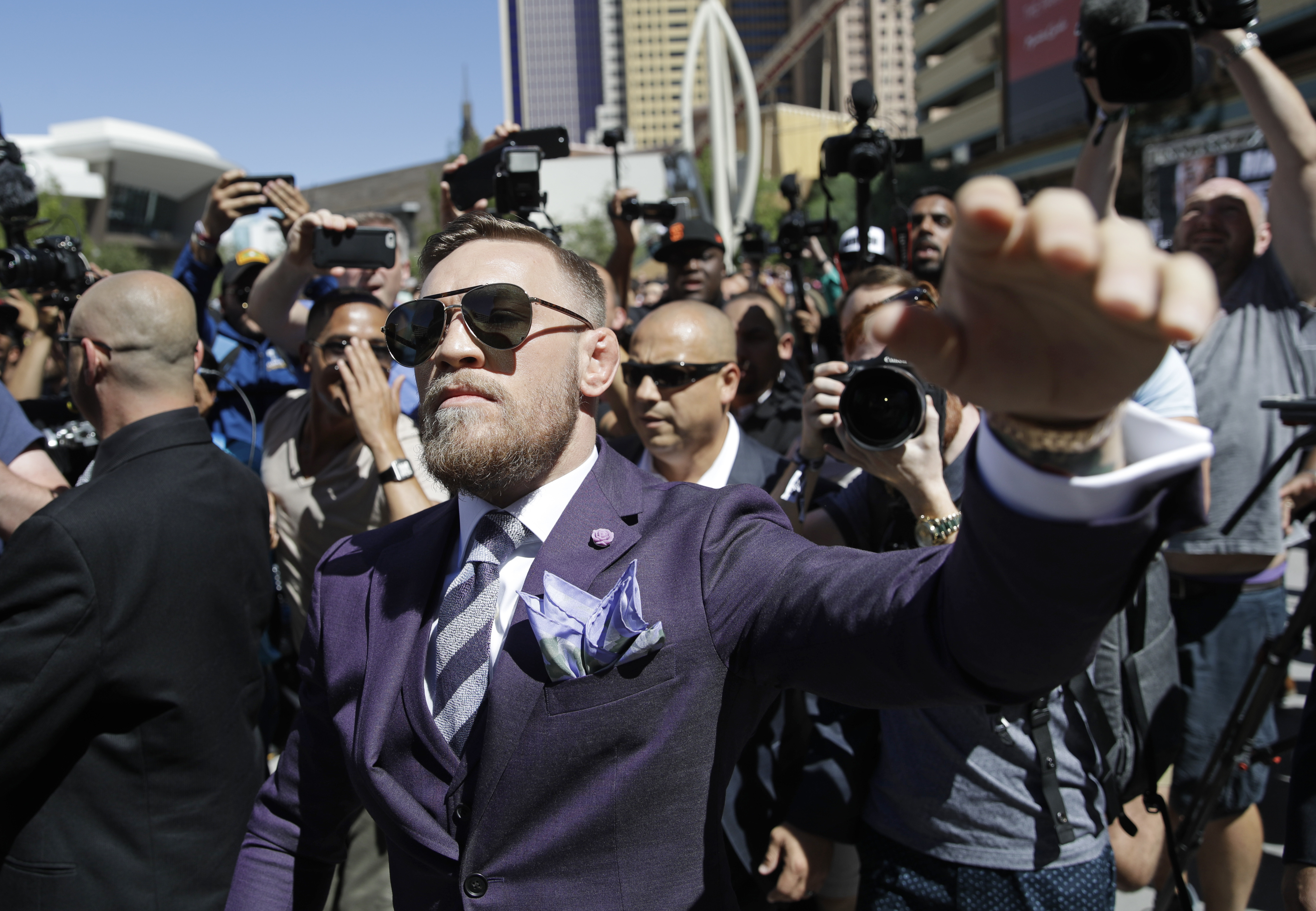 Conor McGregor waves to fans during the arrivals for their fight. (AAP)