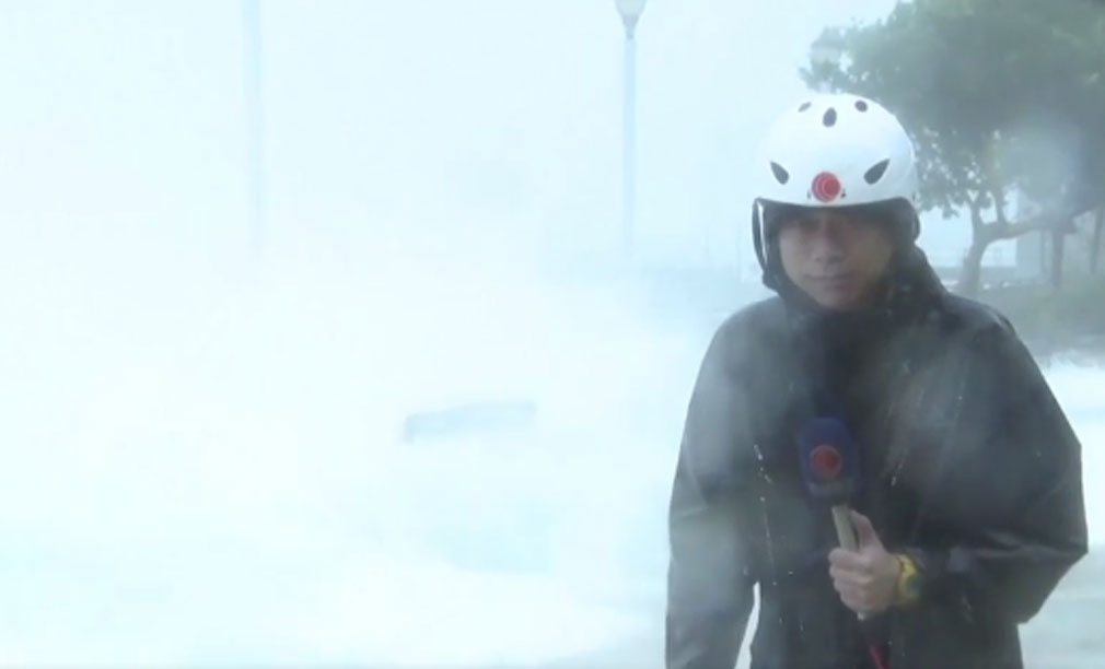 TV presenter reporting on typhoon knocked off feet by wave