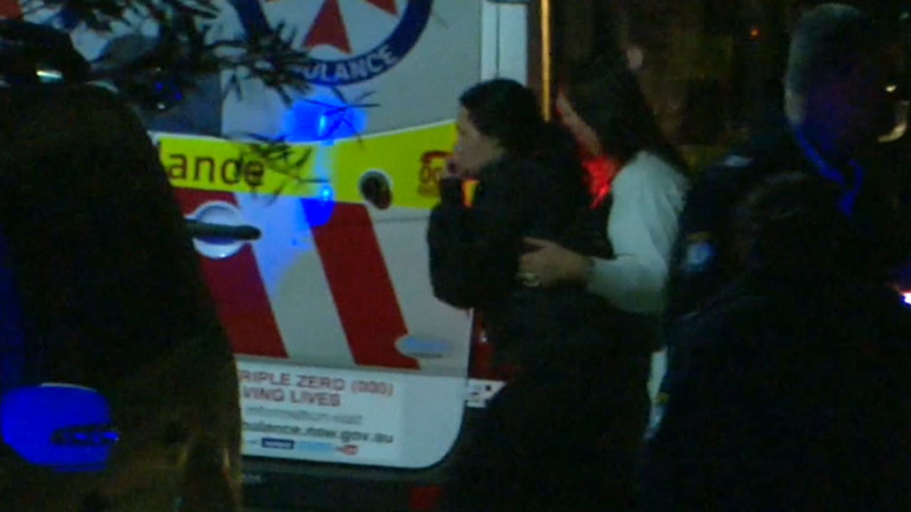 The girl's mother outside the home on Sunday night. (9NEWS)