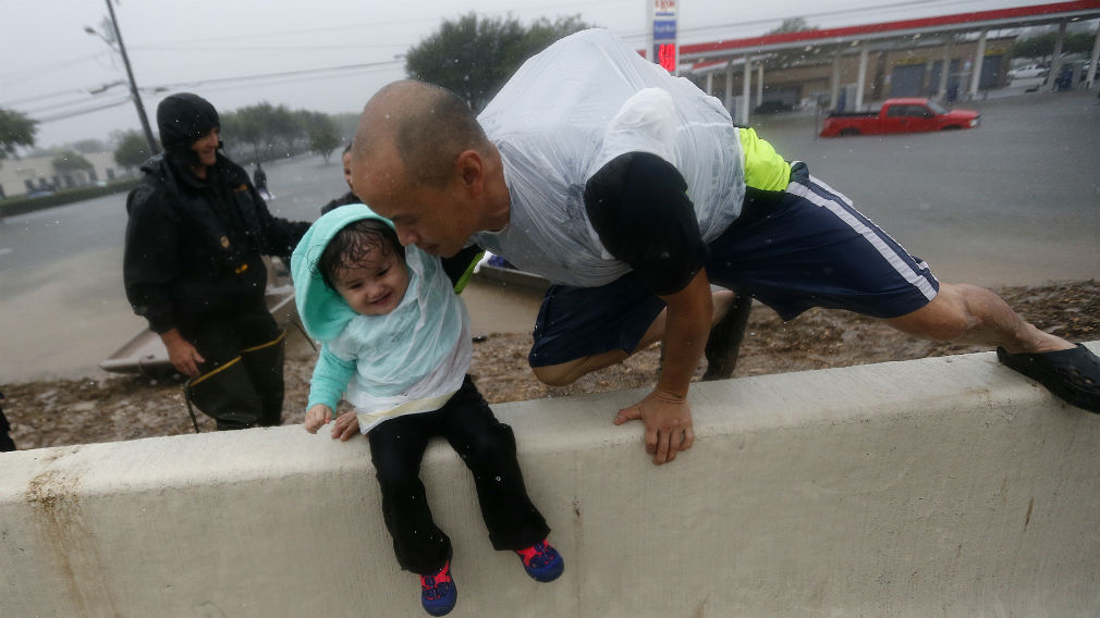 Vinh Nguyen rests his daughter Kailie, 18 months, as he hops over a highway divider after being rescued in boats by the Louisiana Department of Wildlife and Fisheries. (AAP)