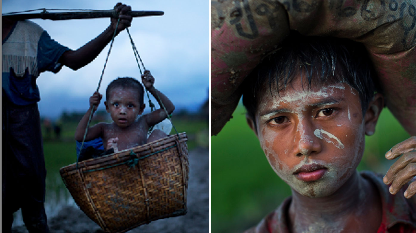 A Rohingya boy is carried in a woven basket as another balances a sack of belongings on his head. (AAP)