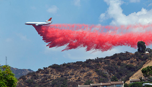 A firefighting aircraft douses the fires with anti-accelerant. (Associated Press).