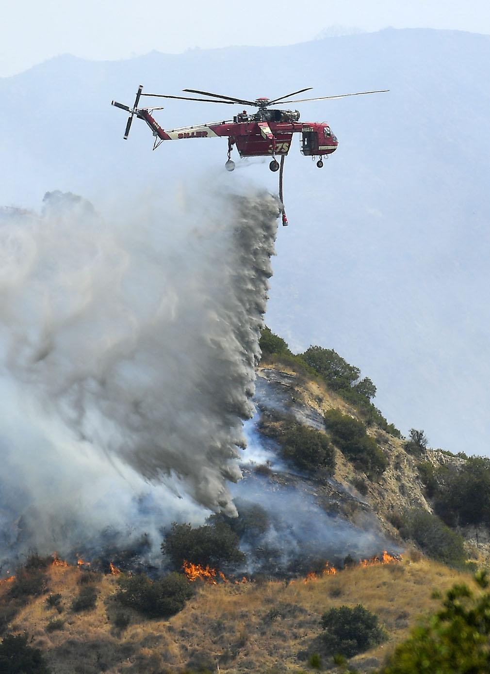 A Skycrane helicopter drops water on a hotspot in Burbank, California. (Associated Press)