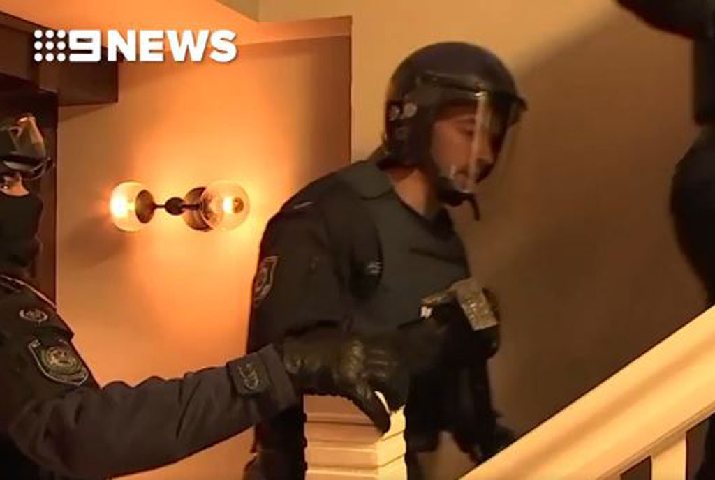 A police officer takes an axe to break down a door during the Kings Cross raids today.