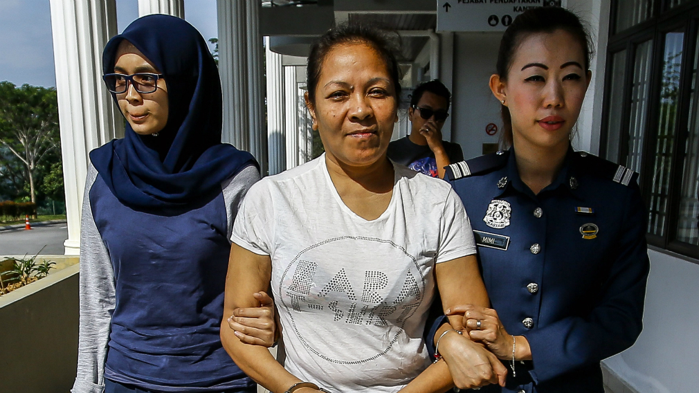 Australian Maria Elvira Pinto Exposto is escorted by police outside the magistrate court in Sepang.