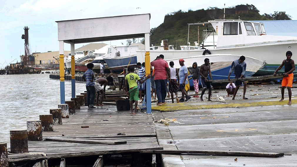 People recover broken parts of the dock after the passing of Hurricane Irma, in St. John's. (AAP)