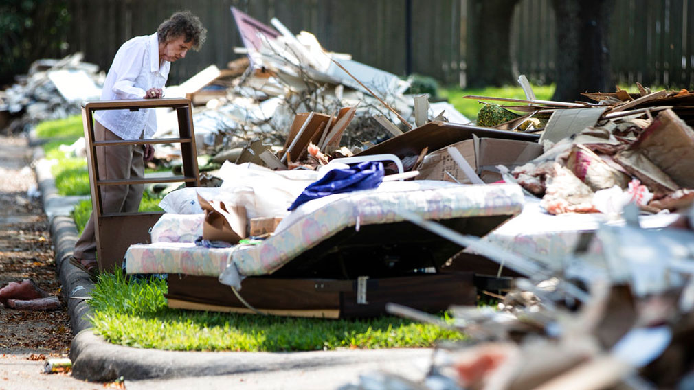 Resident Antoinette Porcarello views her flood-damaged possessions piled in the front yard in the aftermath of the hurricane. (AP)