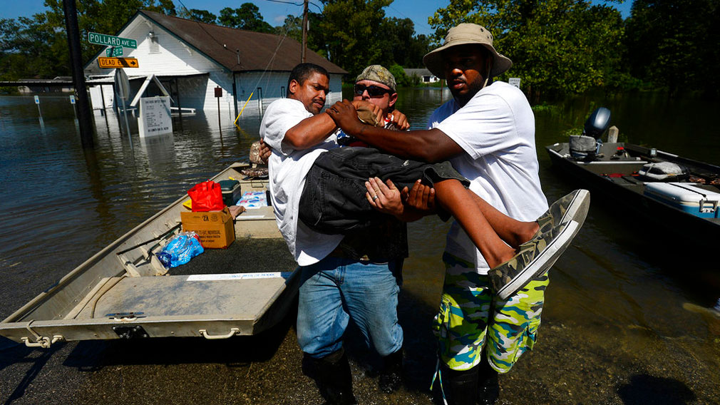 Chris McCarty and Mike Taylor help carry Quintin Sanders, who has cerebral palsy, off a rescue boat in the north end of Beaumont, Texas. (AP)
