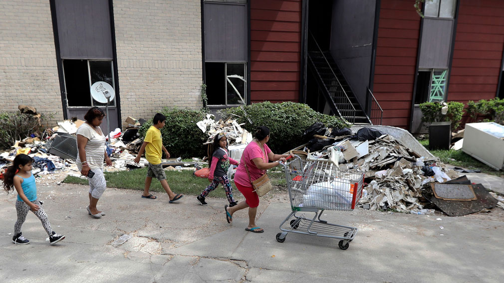 A family walks past debris, which includes a fridge. (AP)