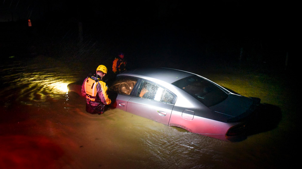 Rescue staff from the Municipal Emergency Management Agency investigate an empty flooded car during the passage of Hurricane Irma through the northeastern part of the island in Fajardo, Puerto Rico. (AP)