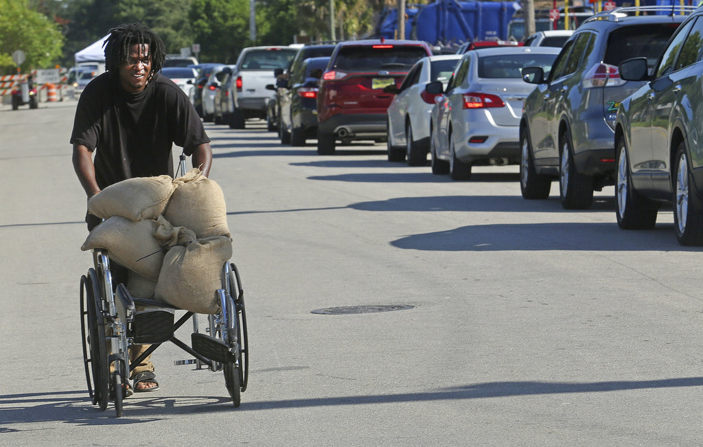 Tyrone Tomlinson, 27, of Orlando, uses a family wheelchair to ferry sandbags to be used on the front porch of their family home. (AP)