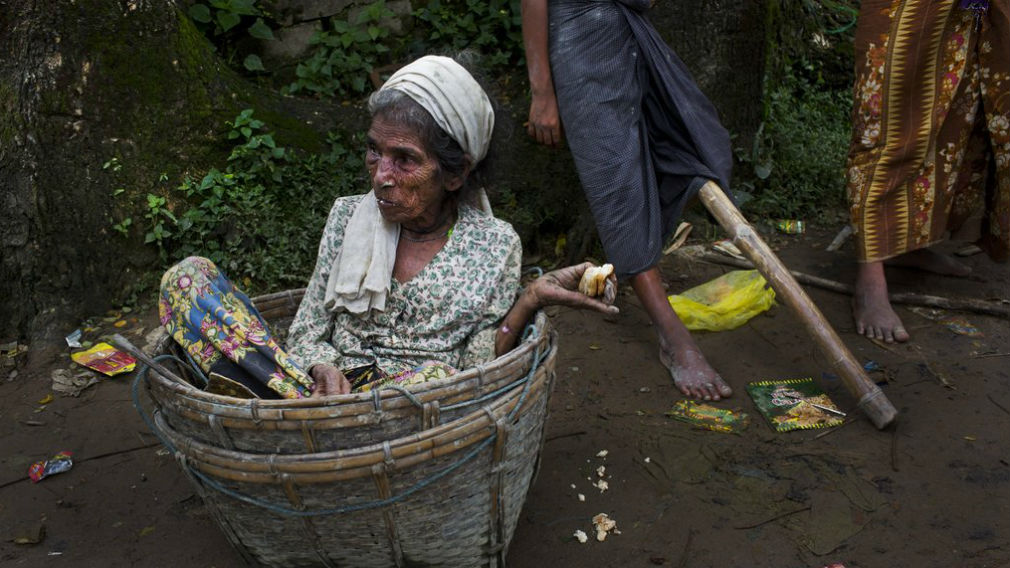 An elderly Rohingya woman sits in a basket that carried her across the border from Myanmar into Bangladesh, after having just arrived at Teknaf border area. (AP)