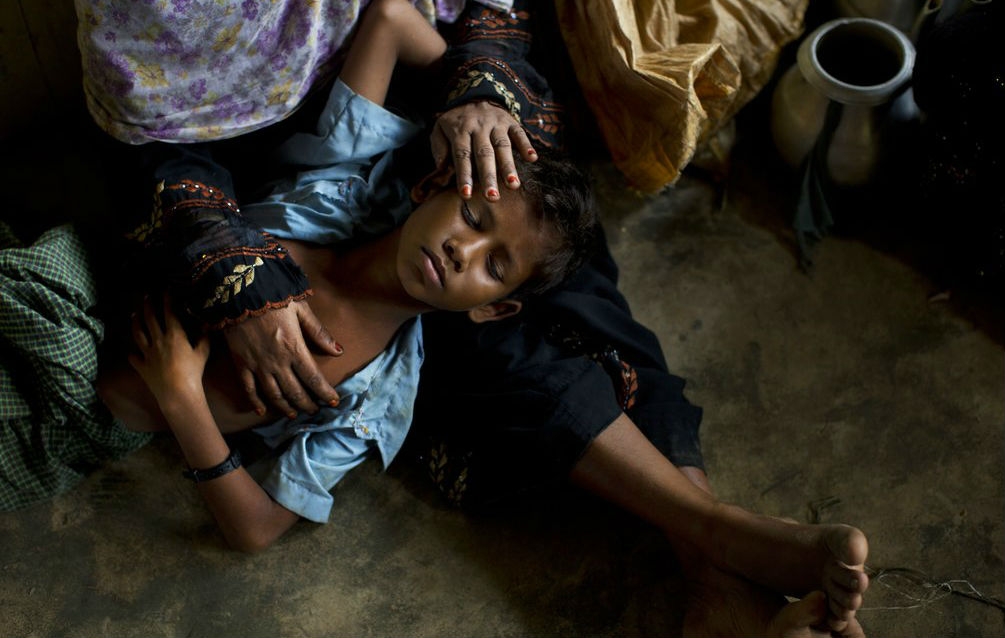 A young Rohingya boy is comforted at a refugee camp. (AP)