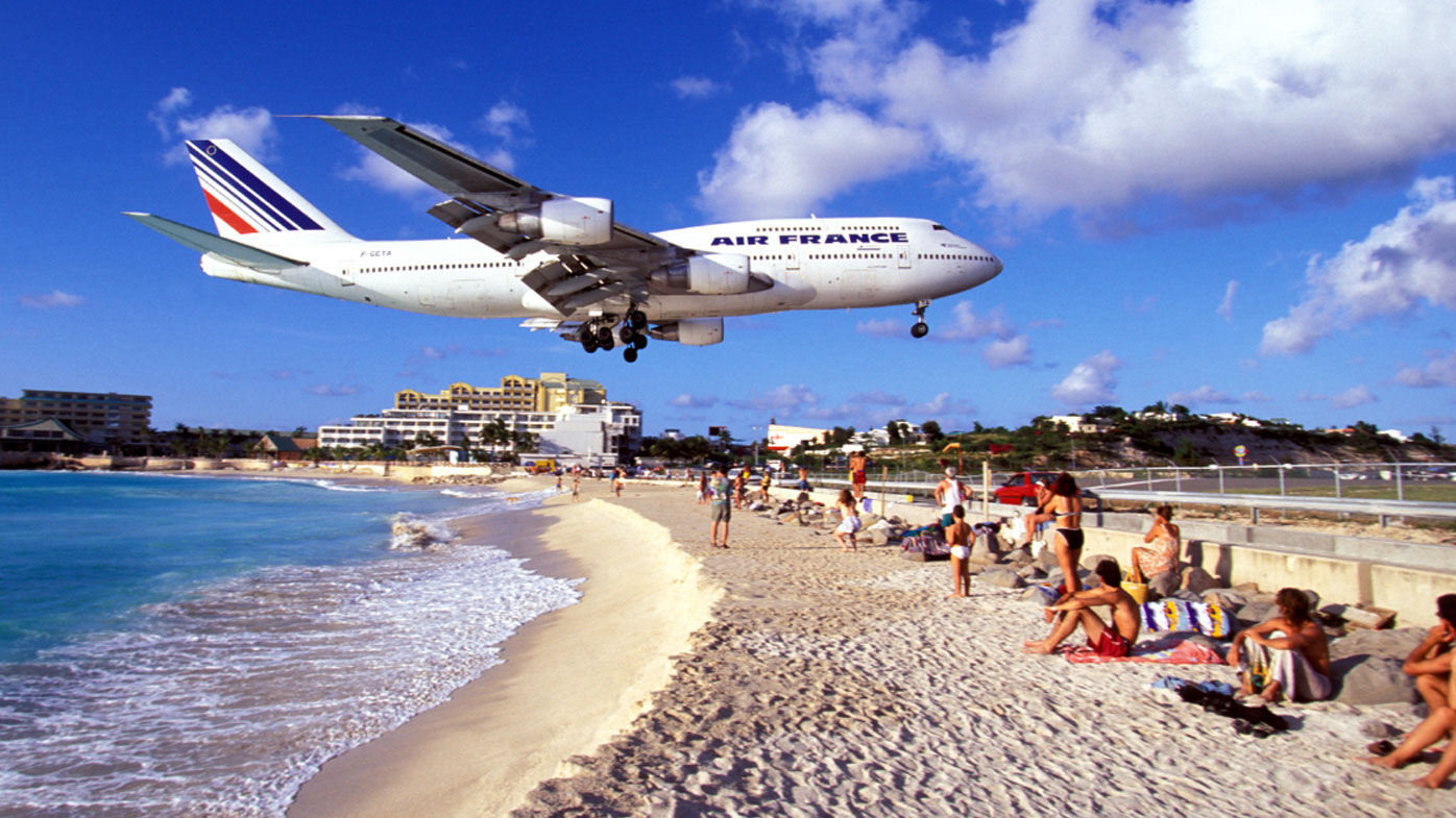 Thrill seekers come to Maho beach in droves to snap a picture with planes flying overhead. (AFP)