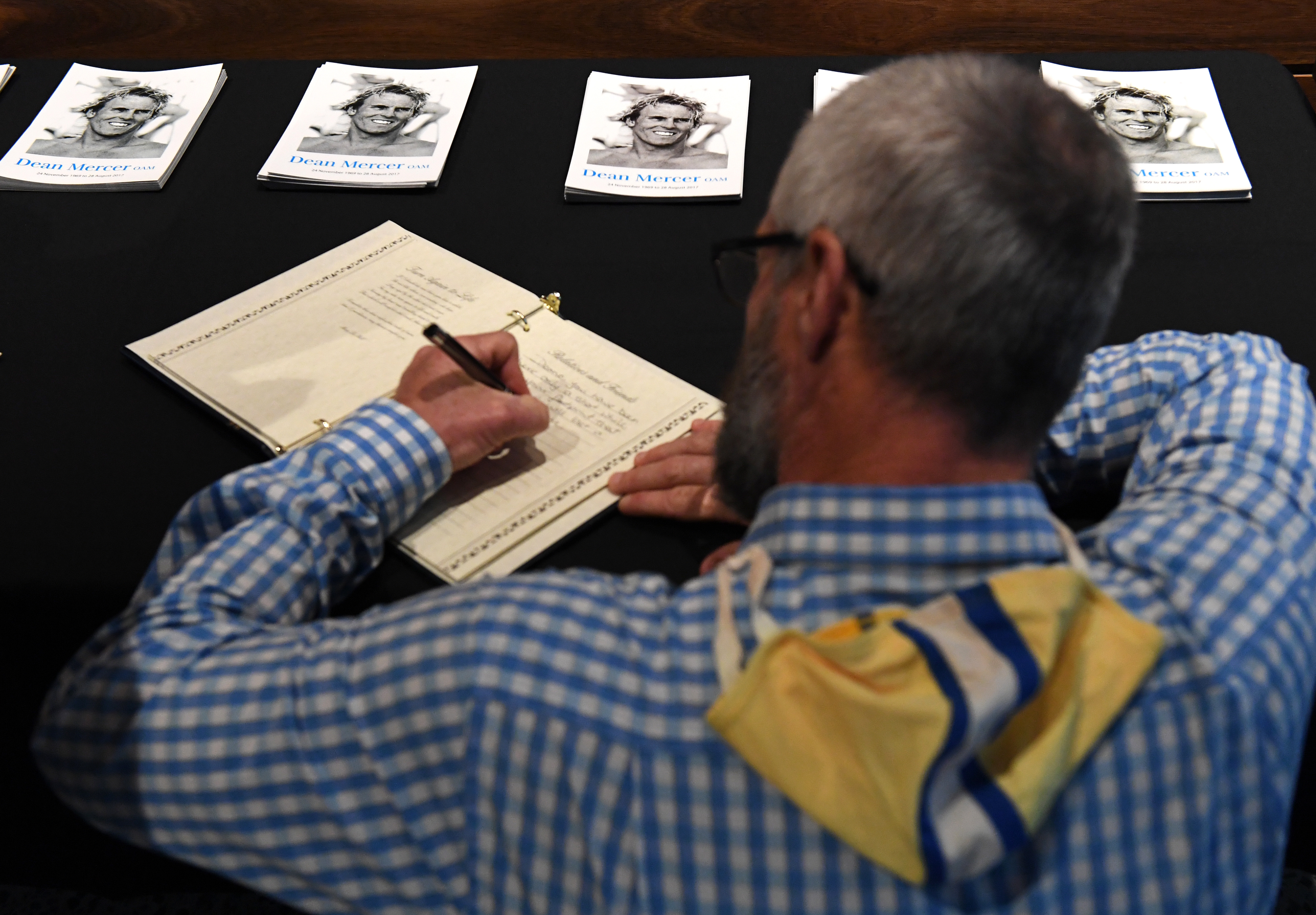 A member of Kurrawa Surf Club signs the condolences book at the memorial service for Dean Mercer on the Gold Coast. (AAP)