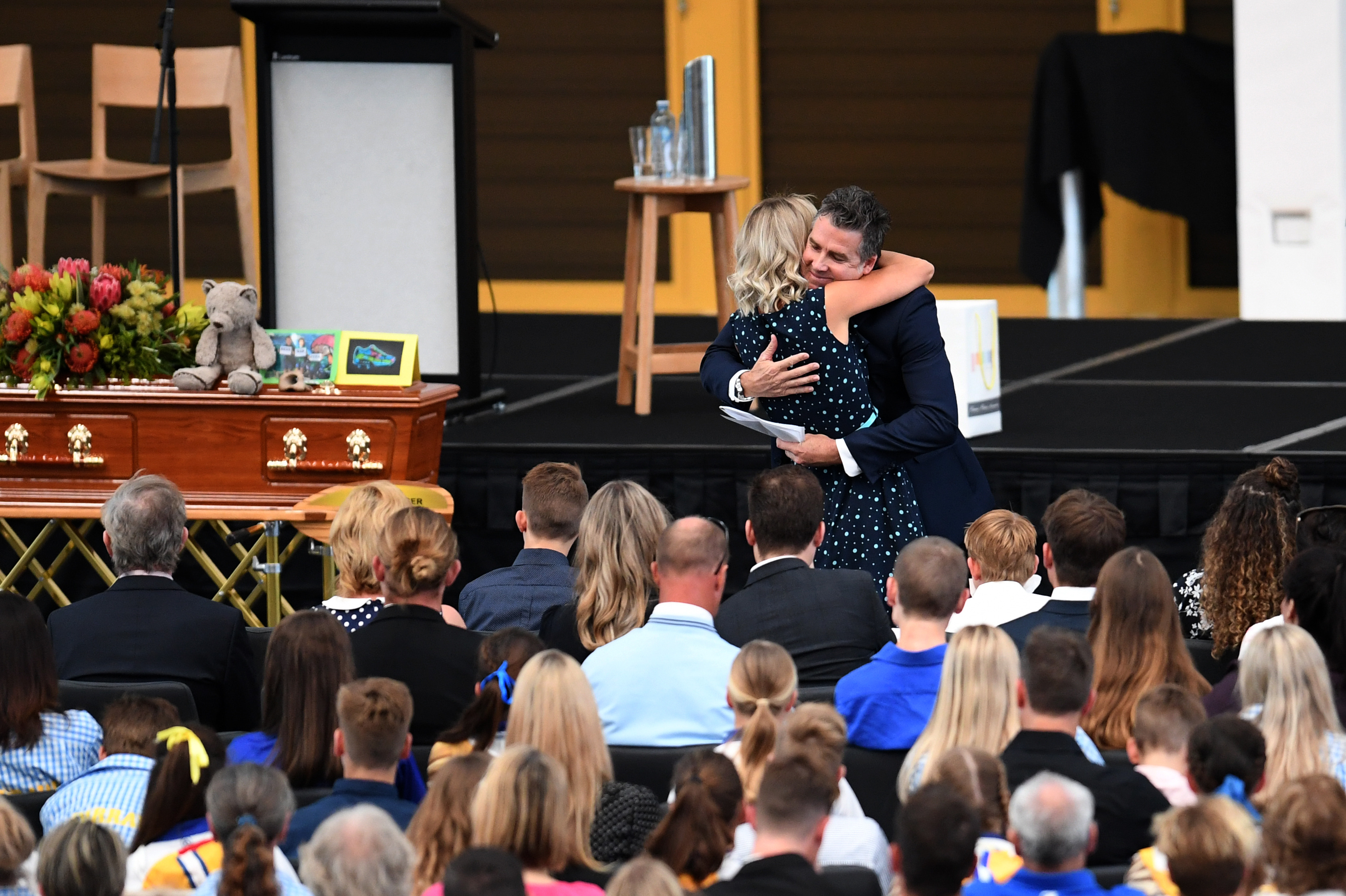 Dean Mercer's brother Darren hugs Reen Mercer during a memorial service for their brother and husband. (AAP)
