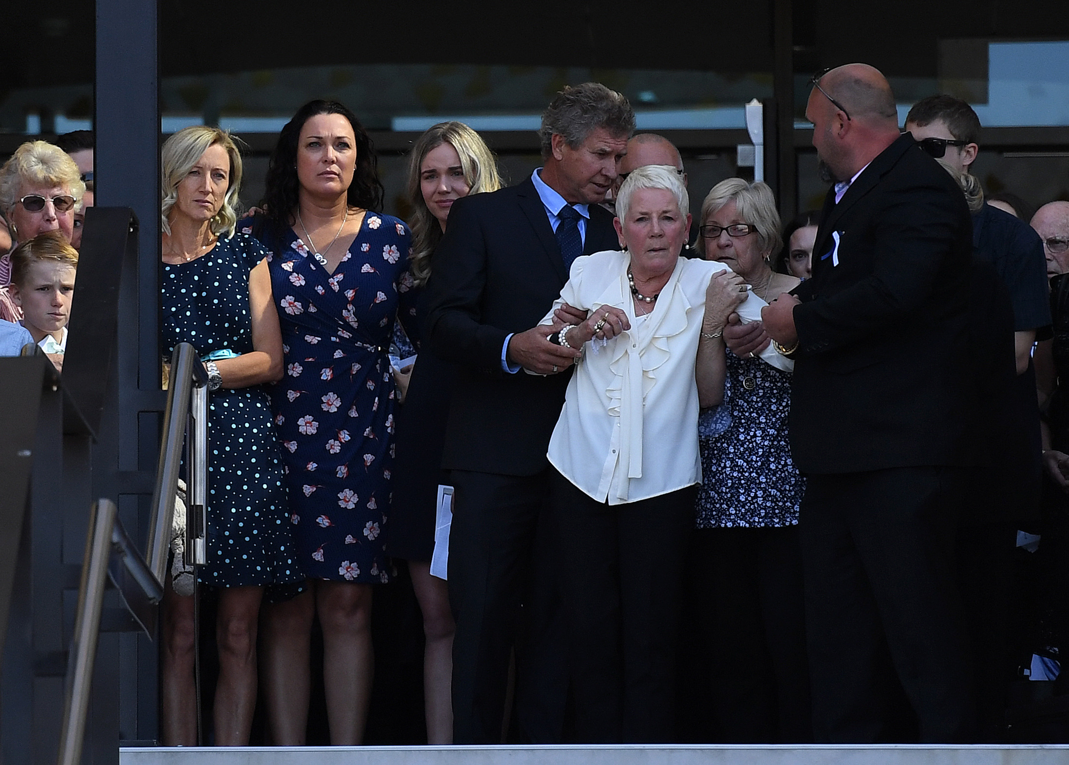 Dean Mercer's wife Reen (2nd left) and his mother Maureen (on right, supported) watch as his coffin is carried away. (AAP)