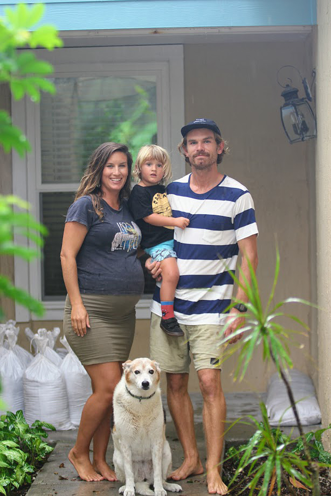 Queensland expatriate Oliver McLeod, his eight month pregnant wife Jennifer, three-year-old son Luca and dog Rubi, outside their sandbagged beach home. (AAP)