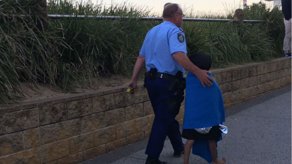 A young boy is assisted by a police officer.  (9NEWS Illawarra)