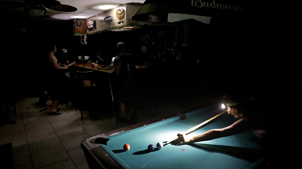 Lisa Borruso plays pool using a headlamp as the power remains out following Hurricane Irma at Gators' Crossroads in Naples. (Associated Press)
