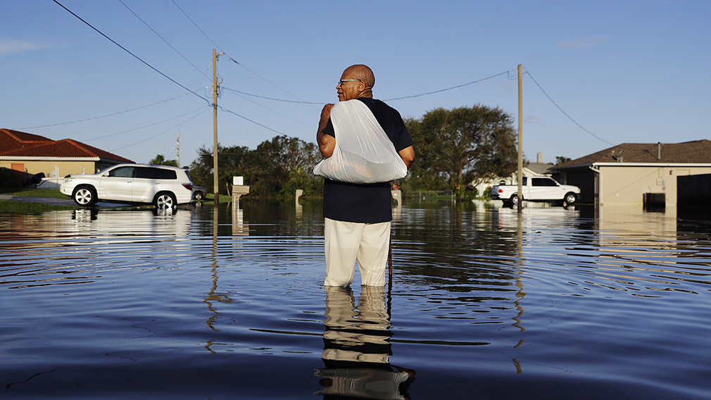 Jean Chatelier walks through a flooded street from Hurricane Irma after retrieving his uniform from his house to return to work today at a supermarket in Fort Myers. (Associated Press)
