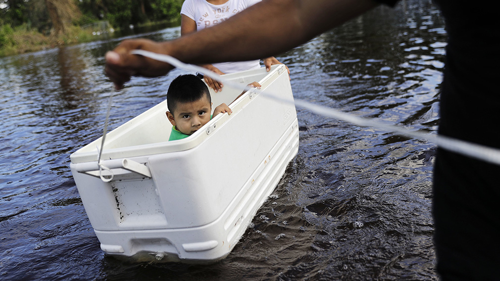 Alfonso Jose Jr., 2, is floated down his flooded street by his parents as the wade through water to reach an open convenience store in the wake of Hurricane Irma in Bonita Springs. (Associated Press)