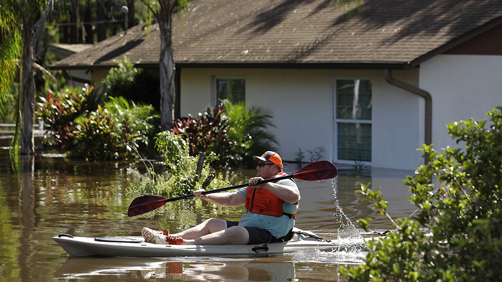 A man paddles a kayak near a flooded home in Lithia. (Associated Press)