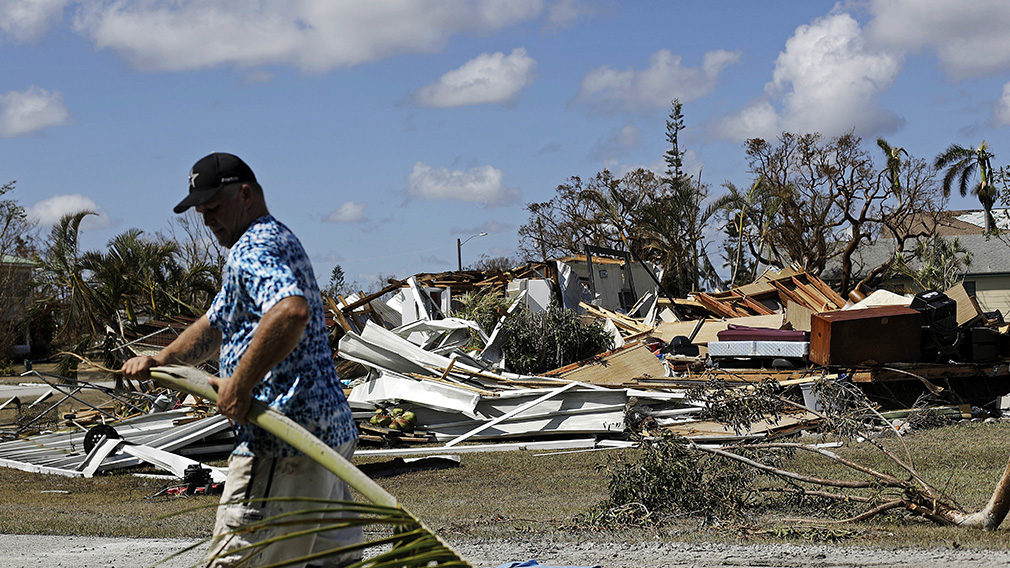 Rob Brehm cleans up debris from his home as a demolished house sits across the street after Hurricane Irma in Goodland. (Associated Press)