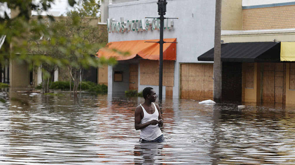 John Duke wades through a flooded street to try to salvage his flooded car in Jacksonville. (Associated Press)