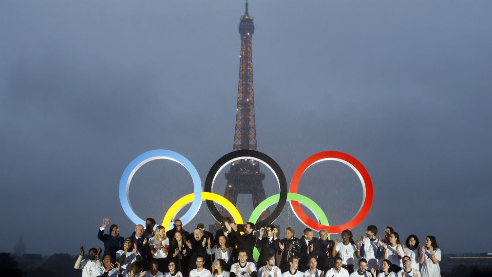 Paris officials pose in front of a display showing the Olympic rings on Trocadero plaza that overlooks the Eiffel Tower, as they celebrate the vote in Lima, Peru. (AAP)