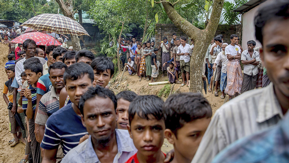 Newly arrived Rohingya Muslims wait for their turn to collect building material for their shelters distributed by aid agencies in Kutupalong refugee camp, Bangladesh. (AAP)
