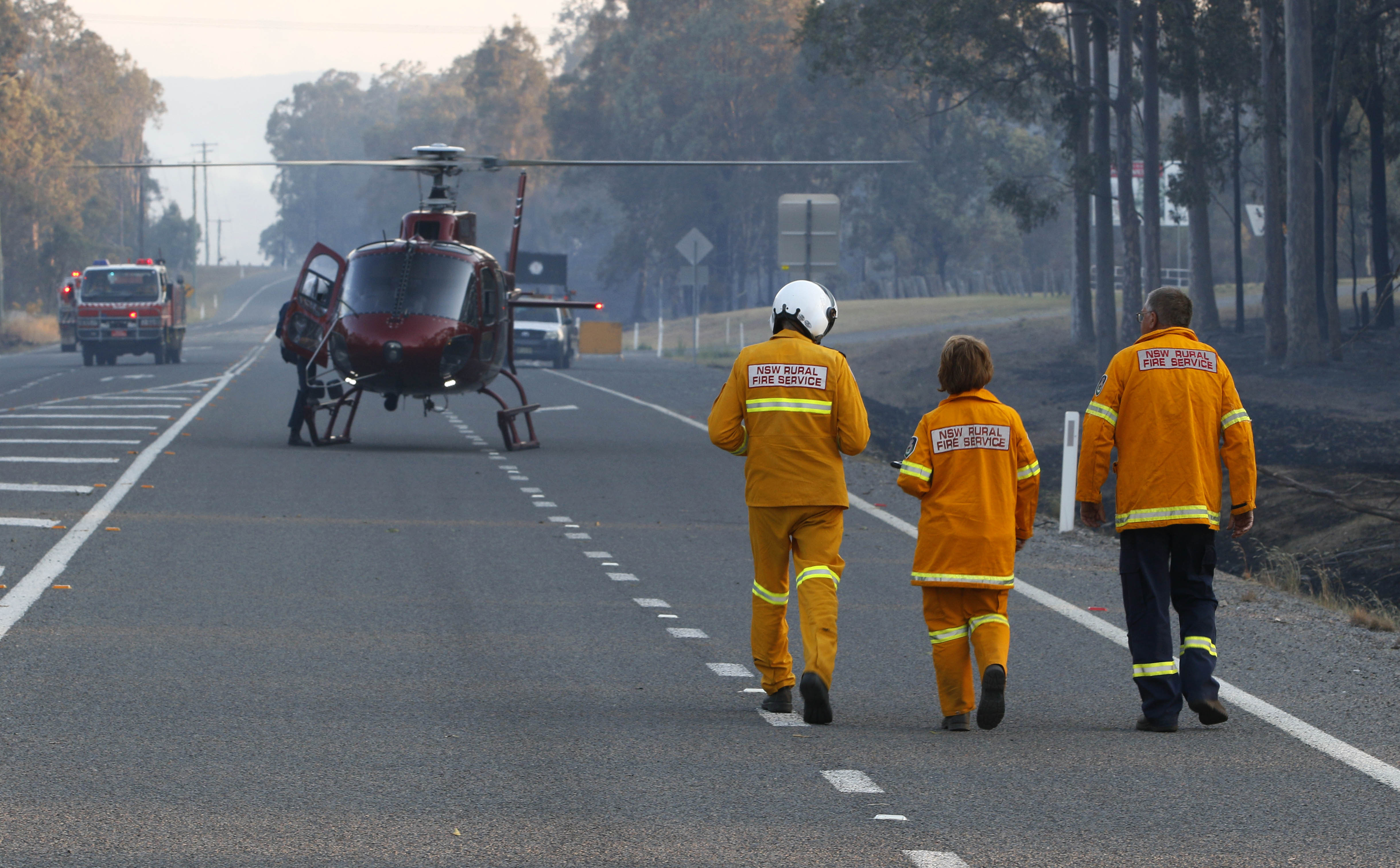 ncident Controller Neil Mutton (right) heads to a helicopter to get an aerial view of a bushfire. (AAP)