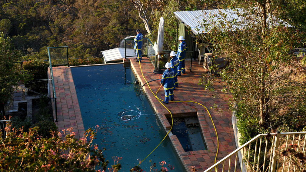 NSW Fire & Rescue Community Fire Unit (CFU) is seen protecting properties under threat from spot fires in Berowra Heights. (AAP)