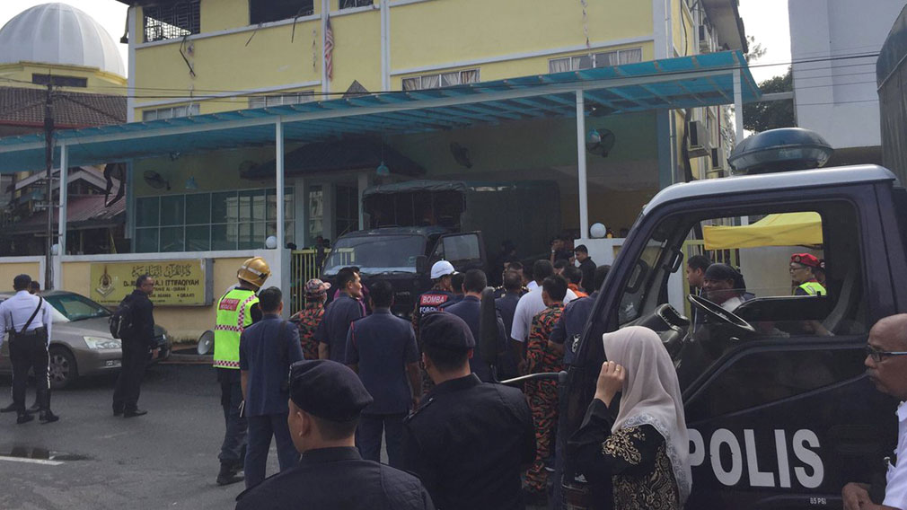 Malaysian police truck waits outside an Islamic religious school following a fire on the outskirts of Kuala Lumpur. (AAP)