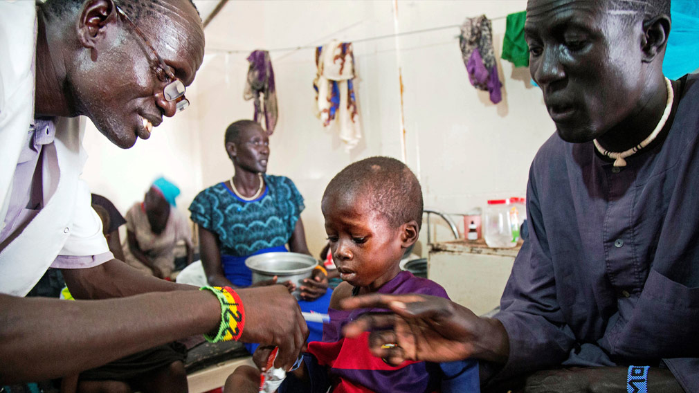 A medical officer from Doctors Without Borders attends to a child with malnutrition in a clinic in Old Fangak Jonglei state South Sudan