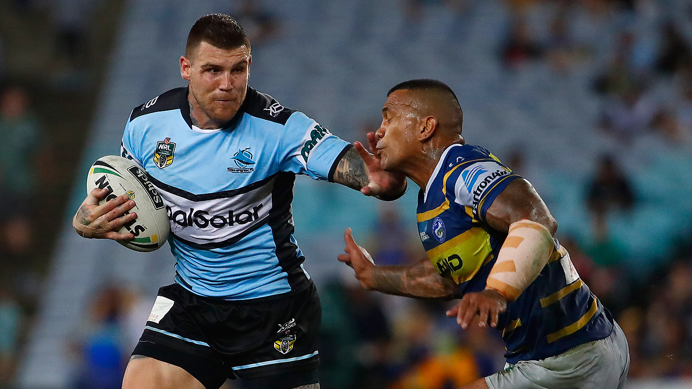 Joshua Dugan of the Sharks evades the tackle of Manu Ma'u of the Eels