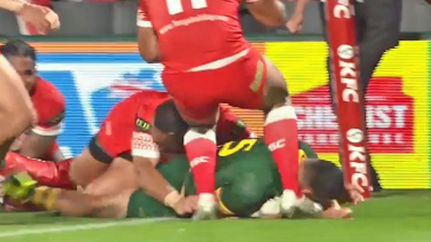 Val Holmes is hit in the head while scoring a try